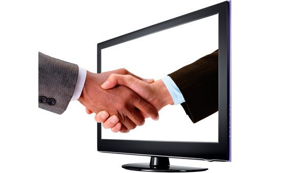 Men shaking hands through a computer monitor